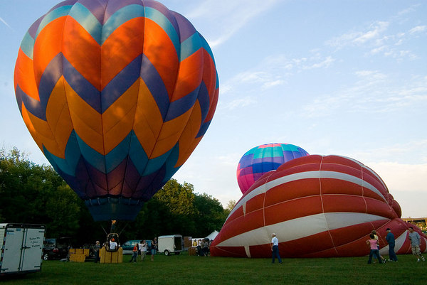 """<font size=""""3"""">The last rays of the Sun peek over the treetops casting an interesting shadow on the leftmost balloon.</font>"""