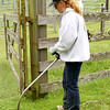 Kathie Goddard mows down the weeds with her weed-eater.