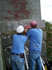 Captain John and Paul work to get a solar panel installed on the North Tower.