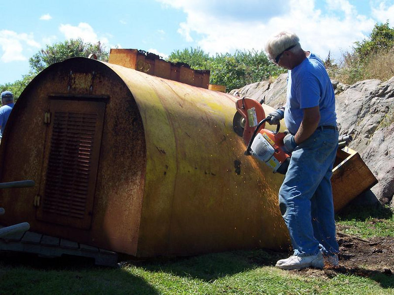 """George Grimes breaking up an old fuel tank, """"watch the sparks."""""""