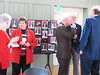 Guests, including the Blairs and the Whites, mingle near the photo displays.