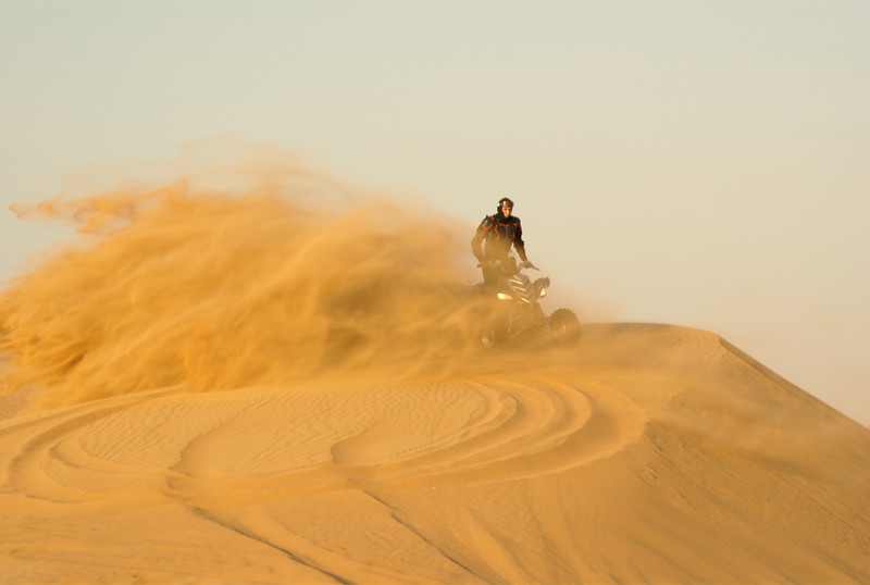 An experienced desert quad-biker, showing off some of his skills. These guys tend to be a little insane ;)<br /> <br /> At the top of a dune in the Sharjah desert, in the UAE.