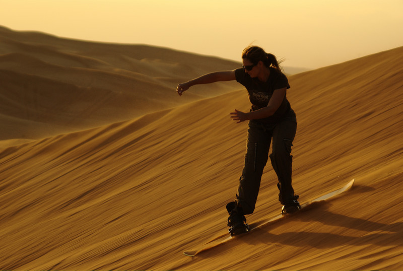 Bianca going down a large sand dune on a sand board!