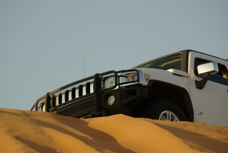 An H3 Hummer parked on the top of a large sand dune in the red desert, in Sharjah, UAE.
