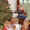 "Trudy adds items to the ""giving tree"" -- donations for ""Toys for Tots"" and the ""Second Harvest Food Bank"" were brought by those who attended the Holiday Barn Party -- everyone was extremely generous this year!"