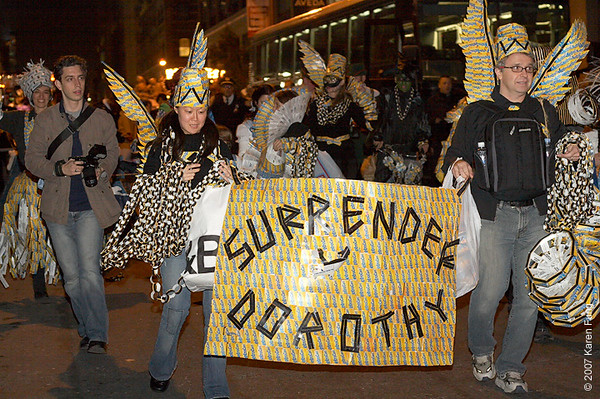 Rosemary and Samir lead with the Surrender Dorothy banner