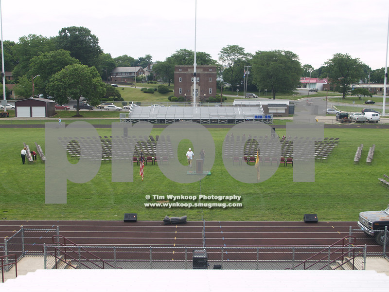School officials and sound engineers work on setting up for the graduation ceremonies Friday morning at on Maloney Field.