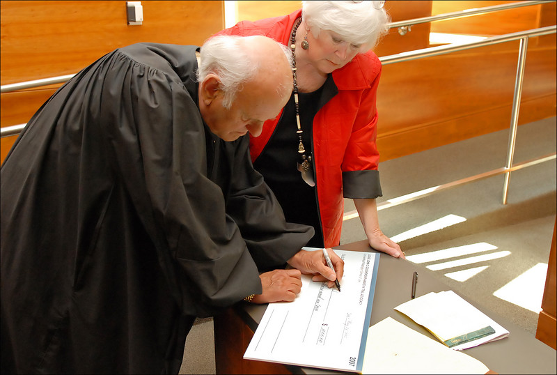 Judge & Mrs. Coughenour sign the prize check for the Best Oral Advocate.