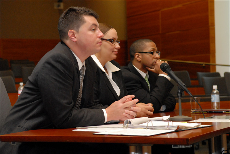 The defense team with pensive defendant.