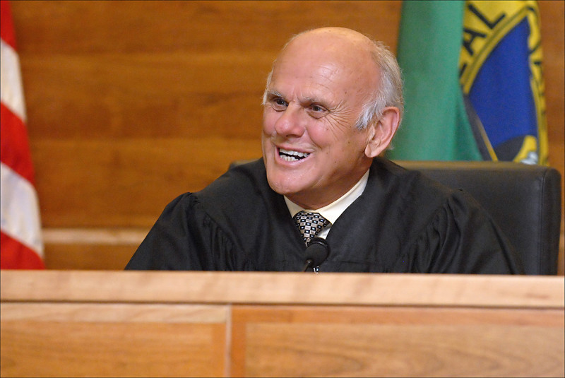 The Judge (smiling).