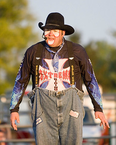 """A rodeo clown (usually known as """"bullfighters"""" among rodeo professionals) quips with the announcer during the bull riding competition at the Boone County Fair on Tuesday night.  According to the Professional Bull Riders website, """"protection bullfighters risk life and limb on a regular basis to save cowboys (and each other) from the heads, horns and hooves of their adversaries in the arena."""""""