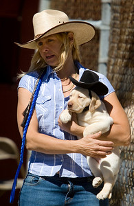 Diana Prince of St. Charles and her 6-month-old yellow Labrador retriever, Elvis, enjoy at day at the Northern Illinois Outlaws cowboy mounted shooting demonstration at the Boone County Fair on Sunday, August 10.