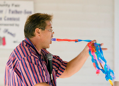 Magician Herb Rosene produces yards of colored streamers from his mouth during his magic show in the entertainment building during the Boone County Fair on Wednesday, August 6.