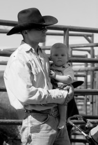 Mark Zullner of Slinger, Wis. and his son Coy wait for Mark's turn to ride a bull at the Big Hat Rodeo on Saturday afternoon.