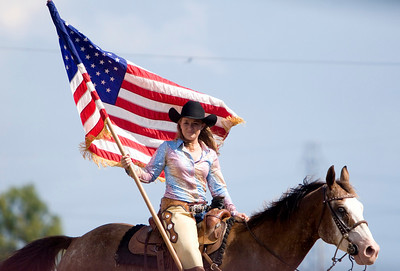 A cowgirl holds the American flag during the national anthem at the Big Hat Rodeo on Saturday afternoon.