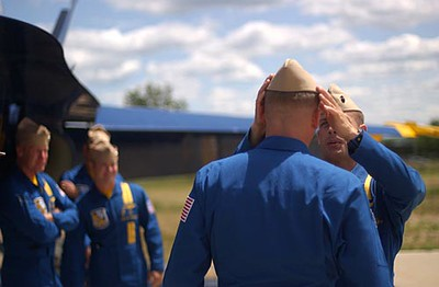 Record-Eagle/Tyler Sipe<br /> Blue Angels Major Nathan Miller makes and adjustment to the cap of one of his peers before having a photo opportunity with Detroit Red Wings hockey player Dallas Drake on Friday afternoon in Traverse City.