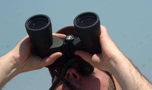 Record-Eagle/Tyler Sipe<br /> Marc McKellar of Interlochen peers through his binoculars to watch members of the United States Army Golden Knight Parachute Team descend from the sky during Saturday afternoon's National Cherry Festival Air Show.