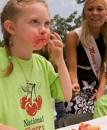 Record-Eagle/Douglas Tesner<br /> Rebekah Keeder, 6, a 2008 National Cherry Festival Pricess from Courtade Elementary School, fills her mouth with pie during the Sara Lee Bakery Kids Cherry Pie Eating Contest Monday. National Cherry Queen finalist Maria LaCross, of Cedar, cheers her on.