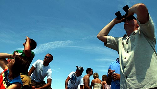 Record-Eagle/Tyler Sipe<br /> Marc McKellar of Interlochen, right, peers through his binoculars to watch members of the United States Army Golden Knight Parachute Team descend from the sky during Saturday afternoon's National Cherry Festival Air Show over Grand Traverse Bay in Traverse City. McKellar and dozens of other people watched the Festival Air Show from Clinch Park Marina break wall.