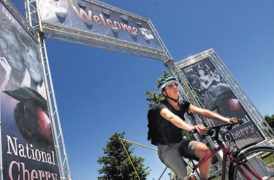 Record-Eagle/Tyler Sipe<br /> Traverse City resident Johanna Schmidt cycles through the National Cherry Festival welcome entrance.