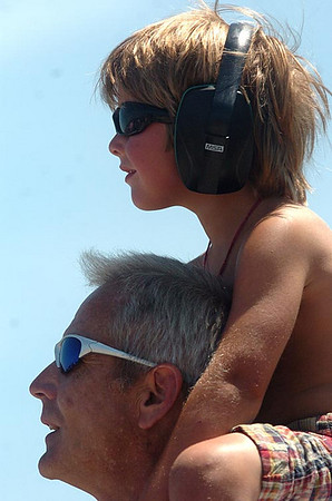 Record-Eagle/Tyler Sipe<br /> Five-year-old Ian Henschell of Rockford enjoys Saturday afternoon's National Cherry Festival Air Show with noise reduction ear phones while on the shoulders of dad Kurt Henschell at the Open Space.