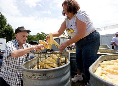 Ralph Bauman (left) and Donna Evans load a metal basket with ears of sweet corn in preparation for cooking during the Coon Creek Country Days corn boil in Hampshire on Sunday, August 3.