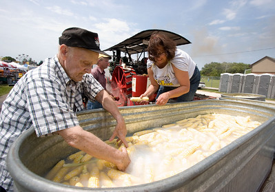Ralph Bauman (left) and Donna Evans gather uncooked, husked sweet corn from a trough filled with water during the Coon Creek Country Days corn boil in Hampshire on Sunday, August 3.  Behind Bauman and Evans is an antique Minneapolis steam engine used to generate enough hot water to boil the 4200 ears of corn prepared for the waiting crowd of people.