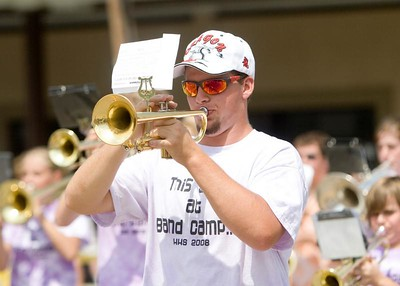 """Hampshire High School senior Ron Bronke plays the trumpet with the rest of the school's marching band during the Coon Creek Country Days parade in Hampshire on Sunday, August 3.  The band practiced for four days at a band camp in Wisconsin to prepare for the parade.  Parade organizers said it has been """"many years"""" since the marching band was part of the parade."""