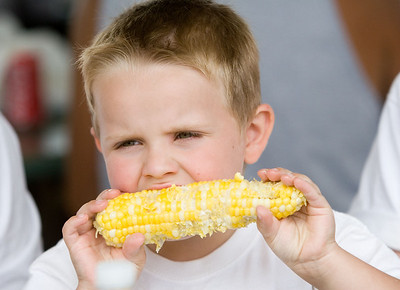 August Rossow, 4, or Hampshire enjoys his second ear of corn during Coon Creek Country Days corn boil in Hampshire on Sunday, August 3.