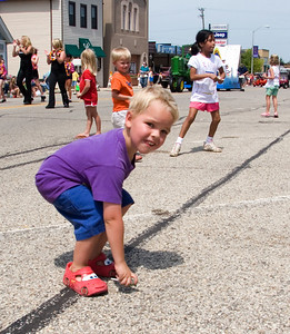 Mitchell McAuley, 4, of Deer Park picks up candy during the Coon Creek Country Days parade in Hampshire on Sunday, August 3.  McAuley and his family were in Hampshire visiting relatives for the day.