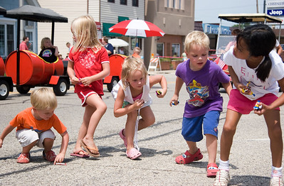 Emmett McAuley, 3 (from left) and his siblings Alzayda, 4, Hattie, 5, Mitchell, 4, and Ellie, 6 scramble to pick up candy  during the Coon Creek Country Days parade in Hampshire on Sunday, August 3.  The McAuleys were in Hampshire visiting relatives for the day.