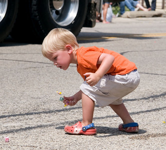 Emmett McAuley, 3, of Deer Park picks up candy during the Coon Creek Country Days parade in Hampshire on Sunday, August 3.  McAuley and his family were in Hampshire visiting relatives for the day.