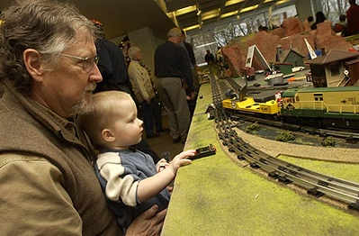 Andrew Zachow, 2, of Traverse City, pushes buttons as his grandfather, Jim Zachow, of Traverse City, provides a better vantage point to watch the passing model trains.
