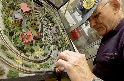 Northern Michigan Railroad Club member Bill Kirschke makes a slight adjustment to his miniscule Markin Z scale train. A new layout at this year's Festival of Trains, Kirschke says he built the traveling case for the German manufactured 1:220 scale train set.