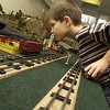Michael Novak, 7, of Traverse City, leans in for a closer look at one of the train set dioramas at the Festival of Trains. Several of the scale model train layouts feature buttons that activate rail road cars, helicopters and even skating rinks.