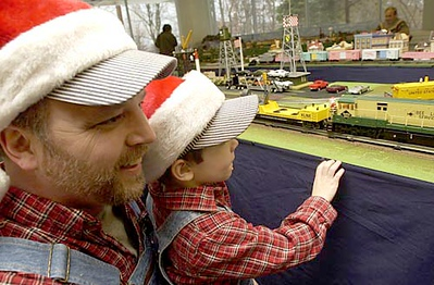 """Wearing matching conductor outfits, Wesley, 4, and Michael Stream drove four hours from Ludington to attend the Festival of Trains. Michael Stream says his son has """"Thomas the Train coming out the ears."""""""