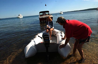 Record-Eagle/Tyler Sipe<br /> Traverse City locals Reed Draper and wife Barb Draper depart the beach west of the Open Space on Friday morning to their 31-foot Sea Ray on Grand Traverse Bay in Traverse City. The couple is spending their holiday weekend on their boat with optimal views of the fireworks and air show.
