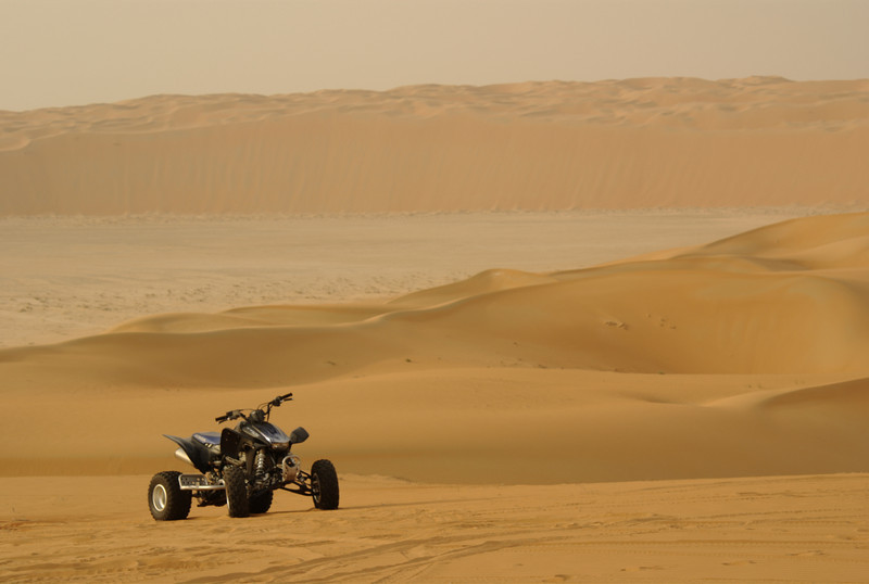 Sean's quad, parked, ready for action, set against the massive Liwa dunes.