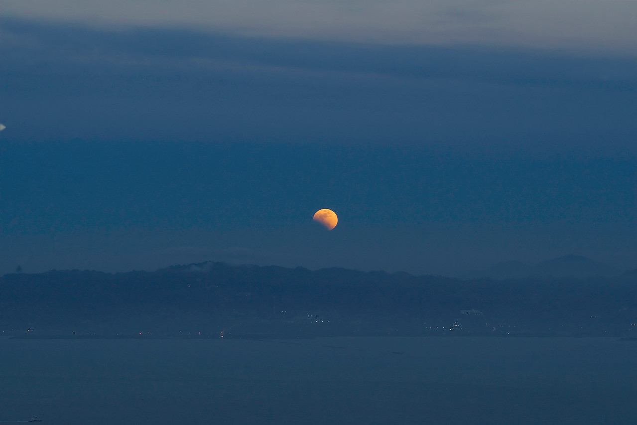 Here's the red moon rising above the East Bay-it's currently partially eclipsed.