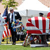 Gold Star Mother Kitty LaPolla is escorted by her husband to put a wreath near the casket of the fallen soldier