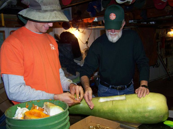 Mac Condill and John tackle a big gourd for seed saving.