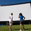 Record-Eagle/Douglas Tesner<br /> Bob Deutsch, president of Outdoor Movies, talks to Jodi Mass, the festival's Open Space manager, in front of the 65-foot inflatable screen.  Deutsch was testing the screen to make sure everything goes smoothly during the first free movie Tuesday night.