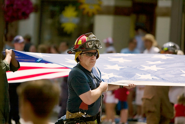 Record-Eagle/Jan-Michael Stump<br /> Members of Grand Traverse Metro Fire Department and the United State Coast Guard carry an American flag in Saturday's National Cherry Festival Cherry Royale Parade