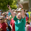 "Record-Eagle/Jan-Michael Stump<br /> Karyann Clark (cq) of Traverse City cheers as members of the Michigan State University band play the ""MSU Fight Song,"" with the Grand Traverse Area MSU Alumni float in Saturday's National Cherry Festival Cherry Royale Parade."