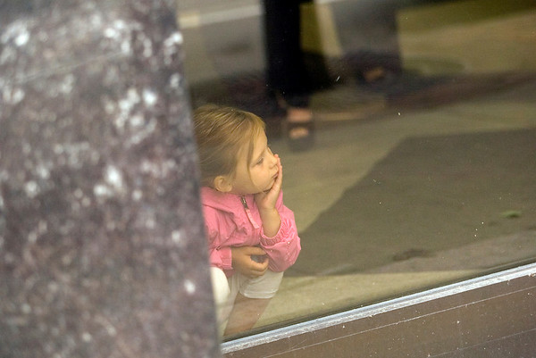 Record-Eagle/Jan-Michael Stump<br /> Ava Keller, 4, of Interlochen looks out the window while her mother Robin visits the bank on their way to the National Cherry Festival on Tuesday morning.