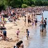 Record-Eagle/Douglas Tesner<br /> Hundreds of boats, swimmers and beach-goers jam the shoreline and water near West End Beach on opening day of the National Cherry Festival.
