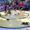 Record-Eagle/Douglas Tesner<br /> Kids pound on the stage to get their turtles moving during the Turtle Races at F&#038;M Park Monday.