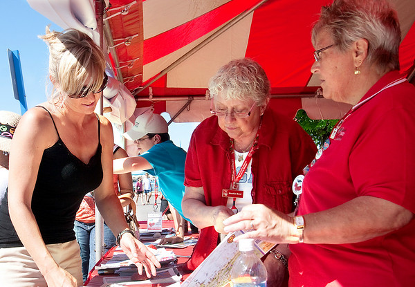 Record-Eagle/Douglas Tesner<br /> Kim Williams, of Waterford, receives help from Cherry Festival volunteers Diane Dennis and Judy Johnson, right.  Johnson is a 15-year volunteer from Grand Rapids.