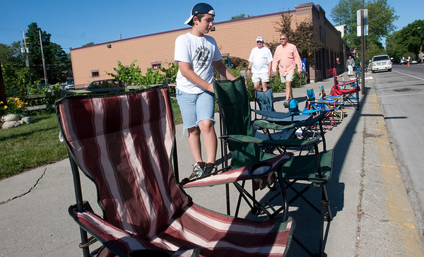 Record-Eagle/Douglas Tesner<br /> At 9:30 a.m., Dominik Baker, 11, checks his street-side lawn chairs put in place for the Touchstone Energy Junior Royale Parade that would be starting some nine hours later.