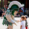 Record-Eagle/Jan-Michael Stump<br /> Sparty, Michigan State University's mascot, stops to high five some fans while marching  with the Grand Traverse Area MSU Alumni float during Saturday's National Cherry Festival Cherry Royale Parade